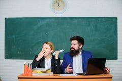 学校材料 企业夫妇使用膝上型计算机和文件 商人和疲乏的秘书 文书工作 办公室生活 backarrow 免版税库存图片