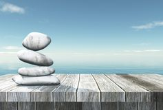 3D balancing pebbles on a wooden table looking out to the ocean. 3D render of balancing pebbles on a wooden table looking out to the ocean Royalty Free Stock Photos