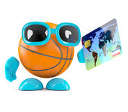 3d Basketball pays with credit card. 3d render of a basketball character holding a credit card Royalty Free Stock Images
