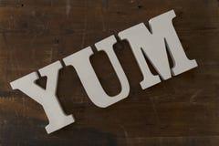 3D beschriftet die Rechtschreibung von YUM Over Wooden Background Stockbilder