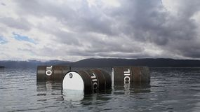 3D black oil drums floating on sea surface. With stormy sky and mountains in background Stock Image