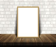 3D blank picture frame on a wooden table leaning against a brick. 3D render of a blank picture frame on a wooden table leaning against a brick wall Stock Photos
