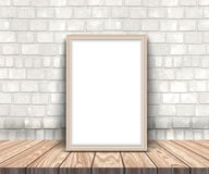 3D blank silver picture frame on a wooden table leaning against. 3D render of a blank picture frame on a wooden table leaning against a brick wall Stock Images