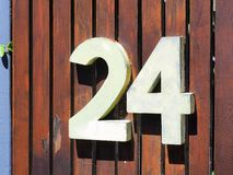 3D House Number, No 24. A 3D block house street number, 24, on a brown wooden gate or fence royalty free stock photography