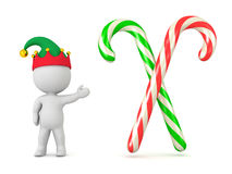 3D Character With Elf Hat Showing Two Colorful Candy Canes Stock Photo