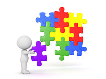 3D Character placing a puzzle piece into jigsaw puzzle. The piece fits in with the other pieces Royalty Free Stock Image