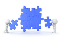 3D Characters placing puzzle pieces into jigsaw puzzle. Image can convey teamwork and cooperation Royalty Free Stock Image