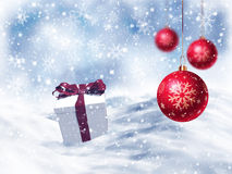 3D Christmas gift nestled in snow with hanging baubles Royalty Free Stock Photo