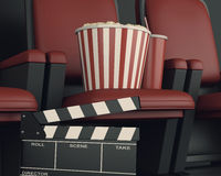 3d Cinema clapper board and popcorn on theater seat. Royalty Free Stock Photos