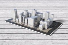 3D city buildings on digital tablet on wooden table Stock Photo