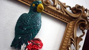 Parrot in frame. 3D color sculpture of the parrot placed in empty golden frame as a interior decoration Royalty Free Stock Photos