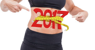 3D Composite image of athlete woman pointing abdominal muscle. Athlete woman pointing abdominal muscle against digital image of 3D new year with tape measure stock photography