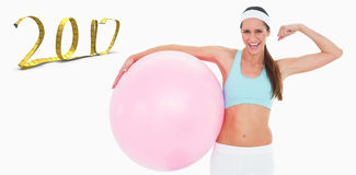 3D Composite image of cheerful fit woman flexing muscles with fitness ball. Cheerful fit woman flexing muscles with fitness ball against white background with Royalty Free Stock Images