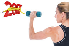3D Composite image of female bodybuilder holding a blue dumbbell Royalty Free Stock Images