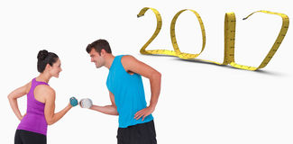3D Composite image of fit man and woman lifting dumbbells. Fit men and women lifting dumbbells against white background with vignette 3D new year royalty free stock photos