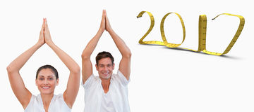 3D Composite image of peaceful couple in white doing yoga together with hands raised stock photo