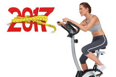 3D Composite image of side view of a beautiful woman on stationary bike Stock Image