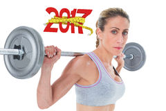 3D Composite image of strong female crossfitter lifting barbell behind head looking at camera Stock Image
