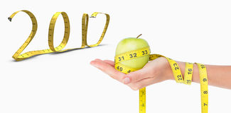 3D Composite image of woman holding an apple with tape measure Royalty Free Stock Photo