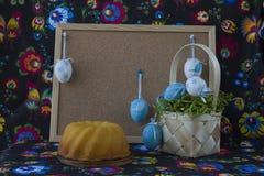 D?coration de P?ques avec les oeufs blancs et bleus sur le fond peint de textile avec le corkboard photographie stock