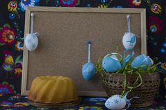 D?coration de P?ques avec les oeufs blancs et bleus sur le fond peint de textile avec le corkboard image stock