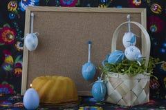 D?coration de P?ques avec les oeufs blancs et bleus sur le fond peint de textile avec le corkboard photo stock