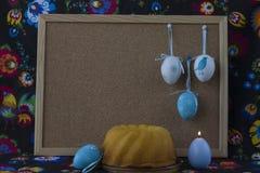 D?coration de P?ques avec les oeufs blancs et bleus sur le fond peint de textile avec le corkboard photographie stock libre de droits