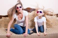 有白肤金发的小女孩坐的观看的3D电影的惊奇年轻美丽的妇女在3D与真实生活特技效果的玻璃 免版税库存照片