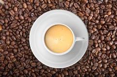 3d, das Tasse Kaffee auf Kaffeebohnen überträgt Lizenzfreie Stockbilder