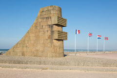 D-day memorial sculpture on Omaha Beach. D-day memorial sculpture with french, british, netherland, norwegian flag; commemorating the liberation of Europe in Stock Photos