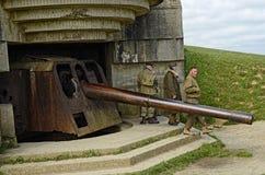 Normandy Gun. Image of ta German gun battery at Longues-Sur-Mer and D-Day reenactors in Normandy, France Royalty Free Stock Photos