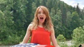D?a de fiesta patri?tico Mujer emocional feliz con la bandera americana en fondo verde del bosque durante día de verano al aire l metrajes