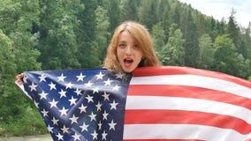 D?a de fiesta patri?tico Mujer emocional feliz con la bandera americana en fondo verde del bosque durante día de verano al aire l almacen de video