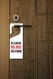 3D: De illustratie van Witboekuithangbord met tevreden stoort tekst het hangen op een handvat van houten deurtoevlucht of hotel n Stock Afbeelding