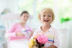 D?a de madres feliz Ni?o con el presente para la mam? imagen de archivo