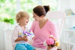 D?a de madres feliz Ni?o con el presente para la mam? fotos de archivo