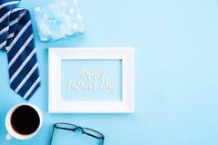 D?a de padre feliz Vista superior del lazo azul, caja de regalo hermosa, taza de café, marco blanco con el texto feliz del día de imagenes de archivo