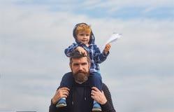 D?a de padres Padre e hijo en el parque Muchacho lindo con jugar del pap? al aire libre El niño se sienta en los hombros de su pa fotografía de archivo