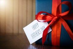 D?a de padres Paquete del regalo envuelto con el papel azul y la cuerda con una cinta roja en fondo de madera foto de archivo libre de regalías