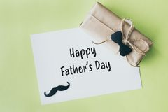 D?a de padres Paquete del regalo envuelto con el papel y la cuerda con una corbata de lazo decorativa en fondo verde fotografía de archivo libre de regalías