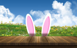 3D Easter bunny ears against a sunny landscape. 3D render of Easter bunny ears against a sunny landscape Stock Image