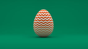 3D Easter Egg with white and orange pattern on green background Royalty Free Stock Image