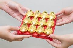 Dé el donante del lingote del oro para la celebración china del Año Nuevo Fotografía de archivo libre de regalías