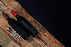 D'en haut du tire-bouchon disposé et peu bouteille de vin rouge sur le bois au-dessus du fond noir image stock