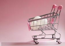 3D festgelegtes Bild Supermarktlaufkatze voll von weißen Bällen auf rosa Hintergrund Verbraucherschutzbewegungskonzeptfoto Stockbild