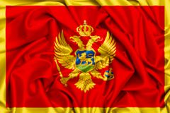 3d flag of Montenegro waving in the wind. Silk texture fabric background Royalty Free Stock Photos