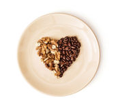 Dê forma ao coração de feijões de café e de nozes descascadas na placa, Val Fotografia de Stock Royalty Free