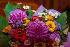 3d frambragt bildcirkelbröllop Två guld- cirklar av brud- och brudgumlögnen på en ovanlig mångfärgad bukett av blommor med tusens royaltyfria foton