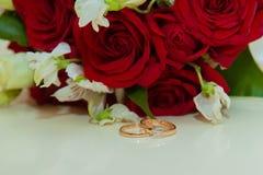 3d frambragt bildcirkelbröllop Två guld- tappningcirklar av brud och brudgum med diamanter och en bukett av röda vita blommor för arkivfoton
