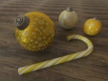 3D framför av guling och guld- feriegarneringstruntsaker med godisrottingen Royaltyfri Bild